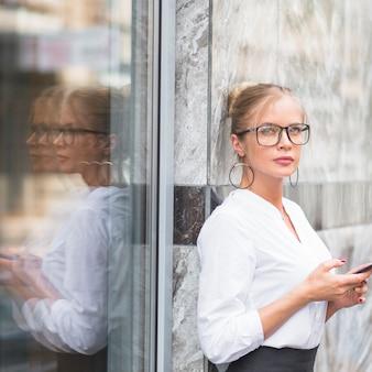 Retrato de una joven empresaria sosteniendo teléfono móvil