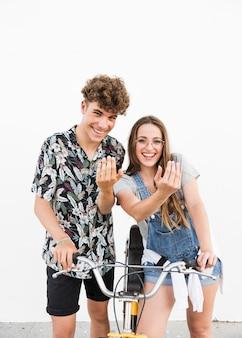 Retrato de una joven pareja sonriente con bicicleta haciendo gesto con la mano