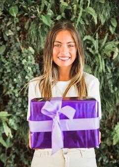 Retrato de una joven sonriente con caja de regalo púrpura
