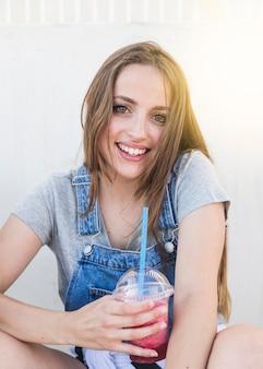 Retrato de una joven sonriente con vaso de jugo mirando a cámara