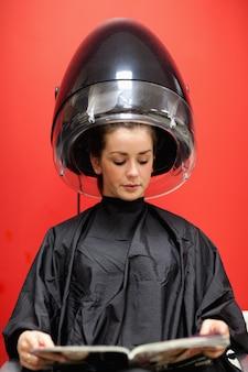 Retrato de una mujer debajo de una máquina de peluquería