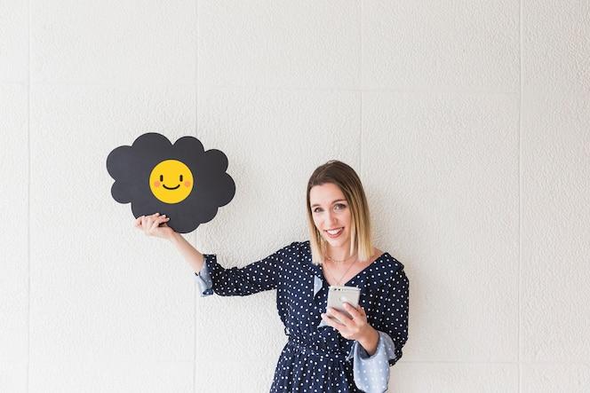 Retrato de una mujer feliz con celular y nube mostrando el icono sonriente