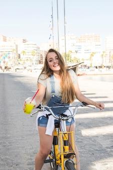Retrato de una mujer joven feliz con vaso de jugo sentado en bicicleta