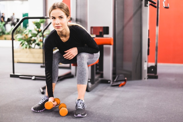 Retrato de una mujer joven que ejercita con pesa de gimnasia