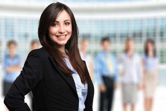 Retrato de una mujer sonriente frente a un grupo de personas