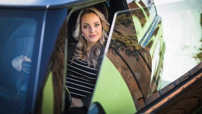 Retrato de una sonriente mujer embarazada sentada en el coche