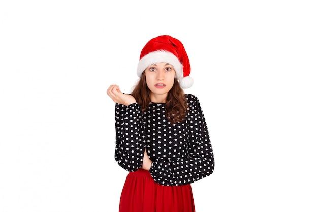 Retrato de decepcionado enojado linda mujer en vestido. chica emocional en santa claus sombrero de navidad aislado