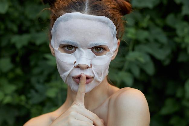Retrato de un dedo de niña cerca de los labios, solicitud de silencio, máscara blanca, primer plano de cosmetología