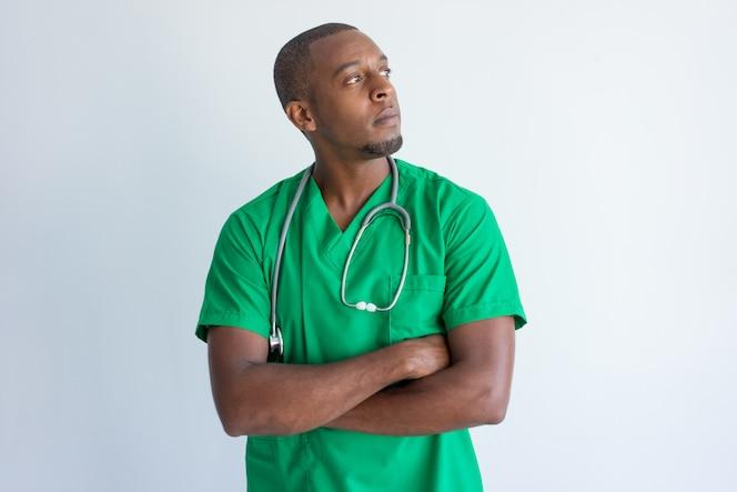 Retrato del doctor afroamericano pensativo que se coloca con los brazos cruzados.