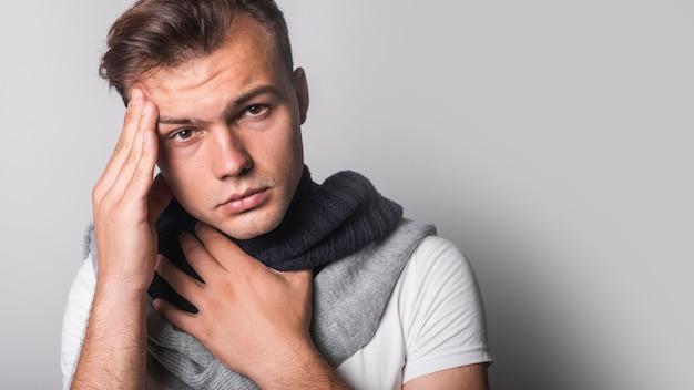 Retrato del hombre que tiene dolor de cabeza contra fondo gris