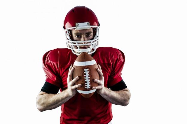 Retrato del jugador de fútbol americano enfocado que sostiene fútbol