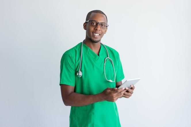 Retrato del médico general feliz con tableta digital.