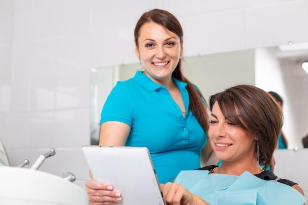 Retrato de un dentista discutiendo un plan de tratamiento con un paciente en una tableta
