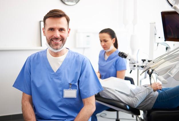 Retrato del dentista masculino sonriente en la clínica del dentista