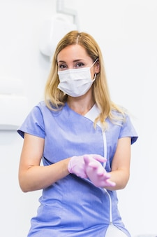 Retrato de un dentista de sexo femenino que lleva guantes rosados