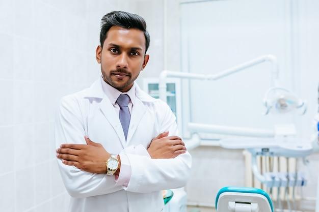 Retrato de un dentista de sexo masculino asiático confidente joven en clínica. concepto de clínica dental