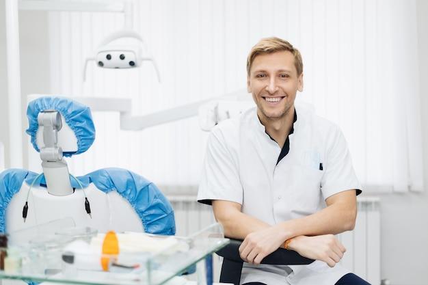 Retrato del dentista sonriente del hombre caucásico que presenta en el consultorio dental moderno.