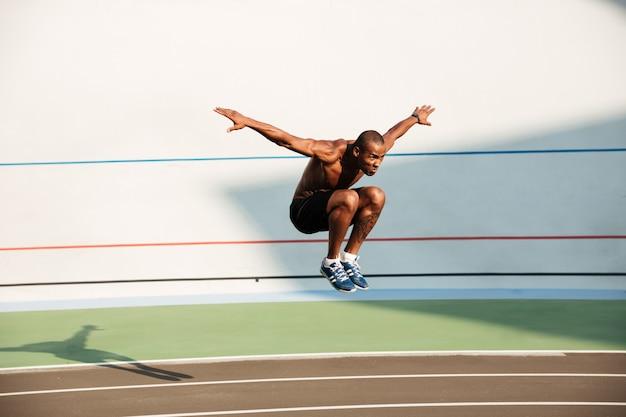 Retrato de un deportista africano medio desnudo fuerte ajuste saltando