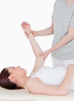 Retrato de una deportista con un brazo estirado por una masajista