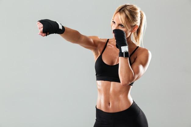 Retrato de una deportista muscular rubia haciendo boxeo
