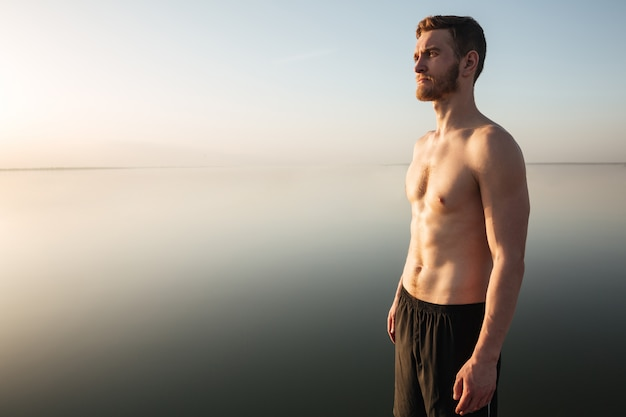 Retrato de un deportista saludable sin camisa de pie al aire libre con agua