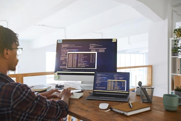 Retrato de desarrollador de ti afroamericano escribiendo en el teclado con código de programación negro y naranja en la pantalla de la computadora y computadora portátil en el interior de la oficina contemporánea, espacio de copia