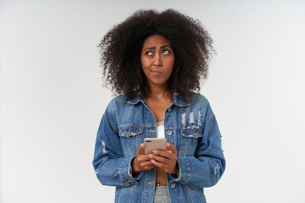 Retrato de desconcertado joven mujer de piel oscura con peinado casual manteniendo el teléfono inteligente en las manos, mirando a un lado pensativamente y frunciendo el ceño, aislado sobre una pared blanca