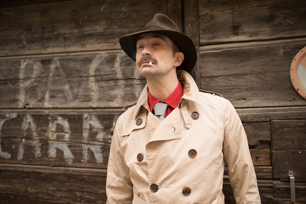 Retrato de un detective cerca de una puerta de madera.