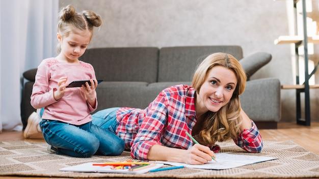 Retrato del dibujo de la madre en el libro mientras que hija que usa el teléfono móvil