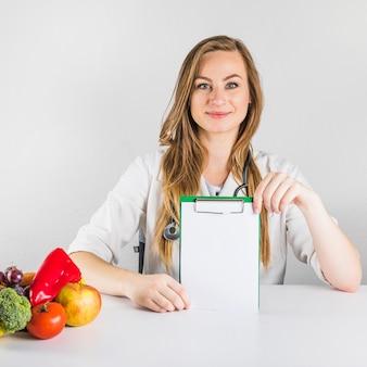 Retrato de un dietista femenino que sostiene el tablero en blanco con la comida sana en el escritorio