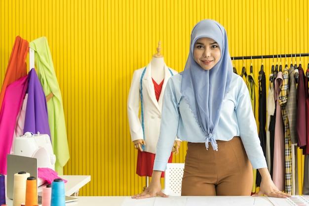 Retrato del diseñador asiático hermoso de la mujer musulmán con el hijab que se coloca en su sala de estudio de trabajo con la máquina colorida de la tela, del vestido, del modelo, del hilo y de costura.