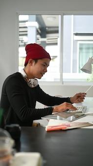 Retrato de diseñador gráfico o fotógrafo utiliza digitalizador y muestra de color en su oficina.