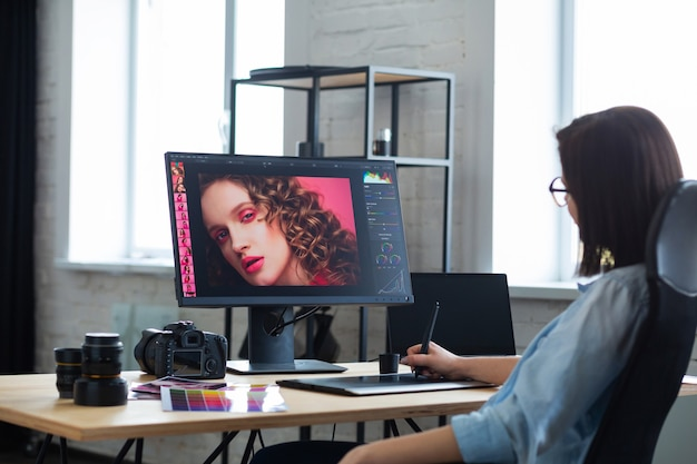 Retrato de diseñador gráfico que trabaja en la oficina con computadora portátil, monitor, tableta de dibujo gráfico y paleta de colores. retoque de imágenes en programa especial. lugar de trabajo de retoucher en estudio fotográfico. agencia creativa.