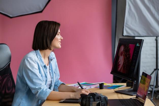 Retrato del diseñador gráfico que trabaja en la oficina con ordenador portátil, monitor, tableta de dibujo gráfico y paleta de colores.