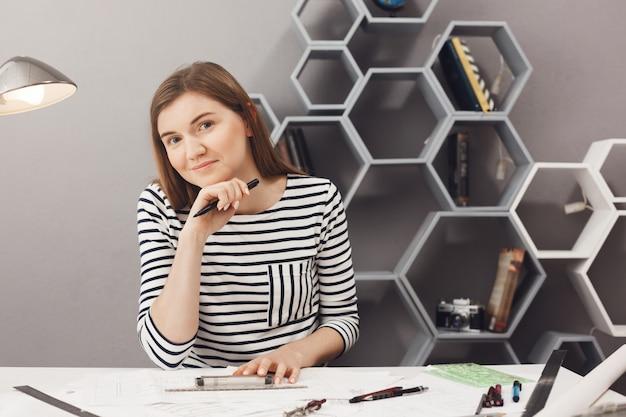 Retrato del diseñador independiente femenino alegre joven de pelo oscuro que se sienta a la mesa en el espacio de trabajo cómodo, que trabaja con la expresión facial relajada y satisfecha