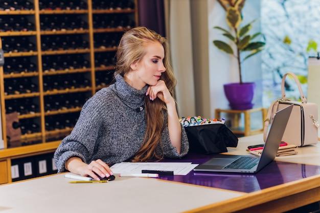 Retrato del diseñador de interiores de sexo femenino sonriente que se sienta en el escritorio de oficina.