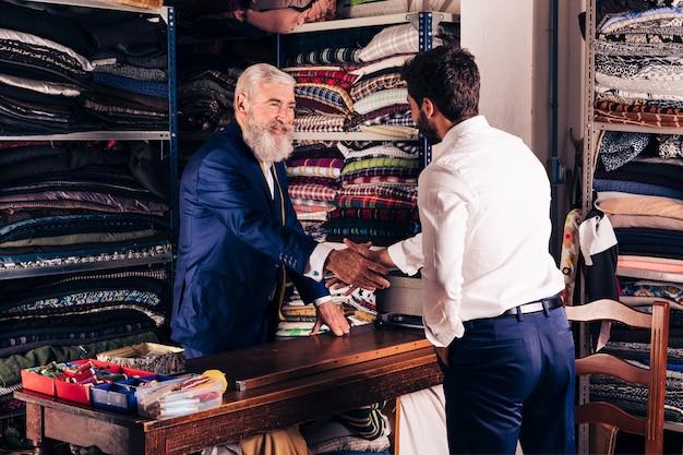 Retrato de un diseñador de moda masculino mayor sonriente que sacude las manos con el cliente en su tienda