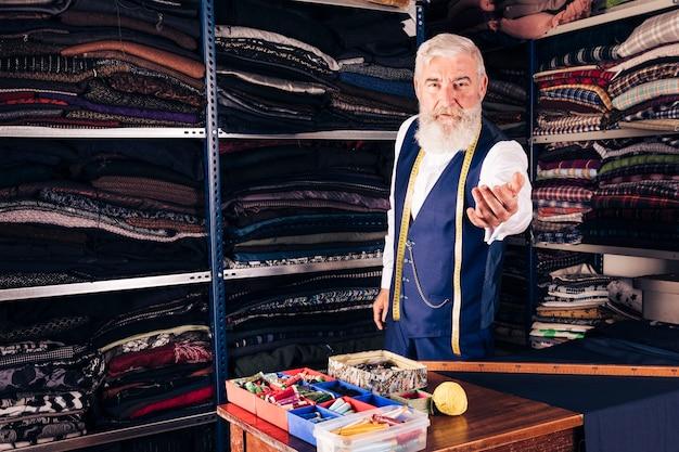 Retrato de un diseñador de moda masculino senior invitando a alguien en su tienda