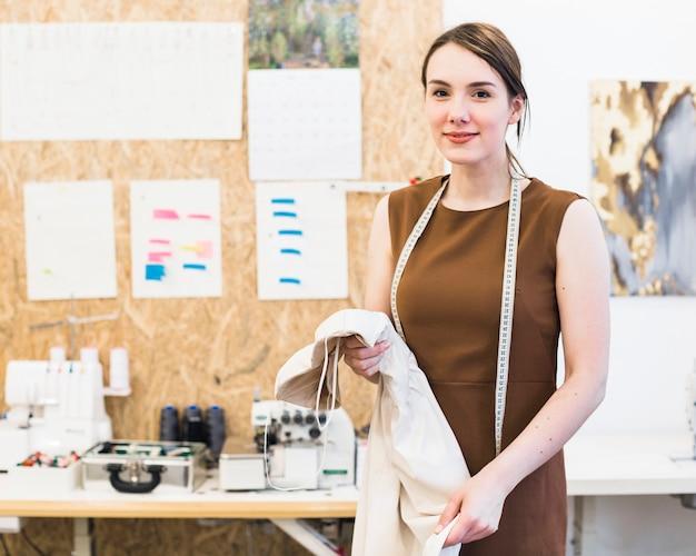 Retrato de un diseñador de moda sonriente con tela