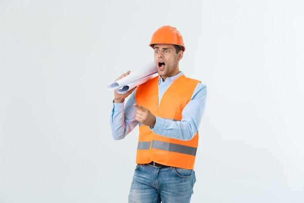 Retrato de diseñador o arquitecto confundido, se siente estresado, nervioso, mantiene la mano en la cabeza, mira fijamente el plano. el hombre exhausto crea un proyecto de construcción solo, tiene algunos problemas.