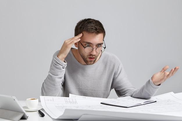 Retrato de diseñador o arquitecto masculino confundido, se siente estresado, nervioso
