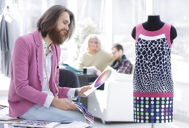 Retrato de un diseñador de ropa sentado en un escritorio en el estudio
