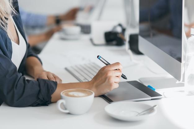 Retrato de diseñador web independiente tomando café en el lugar de trabajo y sosteniendo el lápiz. señora ligeramente bronceada en camisa negra con tableta en su oficina, sentada frente a la computadora.