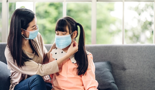 Retrato de disfrutar del amor feliz madre asiática con máscara protectora para niñas asiáticas en cuarentena por coronavirus con distanciamiento social en el hogar
