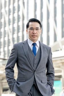 Retrato del distrito de negocios del hombre de negocios asiático, líder de ejecutivos visionarios senior con visión empresarial - concepto de gente de negocios de estilo de vida