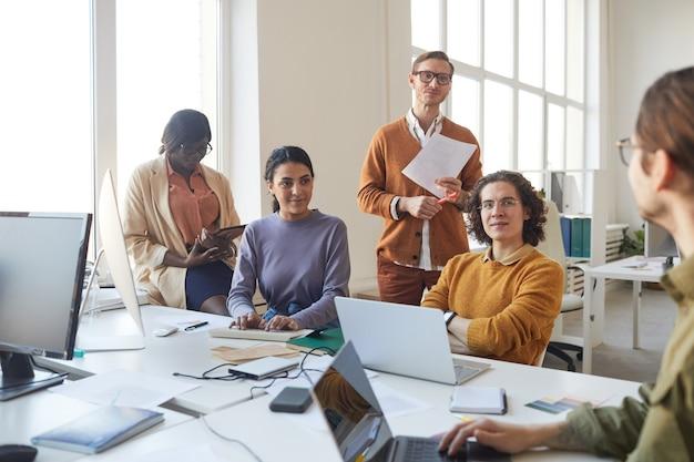 Retrato de diverso equipo de desarrollo de ti discutiendo el proyecto mientras trabajaba en la producción de software en la oficina
