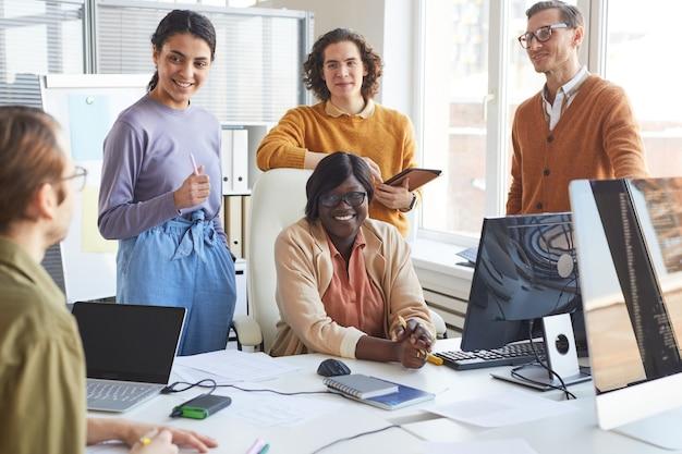 Retrato de diverso equipo de desarrollo de ti discutiendo el proyecto y sonriendo mientras disfruta del trabajo en el estudio de producción de software