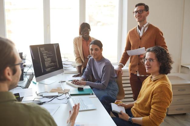 Retrato de diverso equipo de desarrollo de ti discutiendo el proyecto y sonriendo mientras disfruta del trabajo en la producción de software, copie el espacio