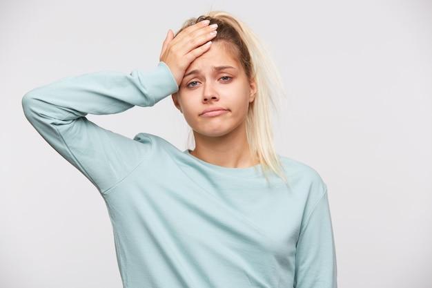 Retrato de divertida linda joven con cabello rubio y cola de caballo viste camiseta azul
