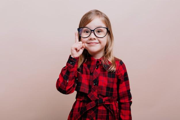 Retrato de divertida niña inteligente lleva gafas y camisa a cuadros levantó un dedo y sonríe en el frente
